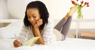 Lycklig svart kvinnahandstil i tidskrift Royaltyfria Foton