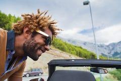 Lycklig svart man som lutar över den konvertibla bilen Arkivbilder