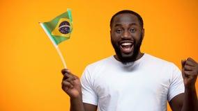 Lycklig svart man som rymmer den brasilianska flaggan, st?ttande landslag f?r fotbollsfan royaltyfri foto