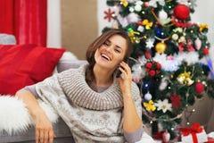 Lycklig talande mobiltelefon för ung kvinna nära julträd Arkivbild