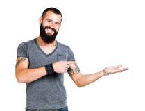 Lycklig Tattooed skäggig man som framlägger och visar Fotografering för Bildbyråer