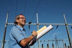 Lycklig tekniker bredvid elektrisk avdelningskontor. Royaltyfri Foto