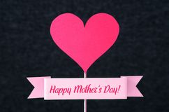 Lycklig text för dag för moder` s på ett band och en röd hjärta Royaltyfri Bild
