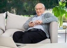 Lycklig textMessaging för hög man till och med Smartphone royaltyfri bild