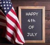 LYCKLIG 4th AV det JULI tecknet och amerikanska flaggan Arkivfoto