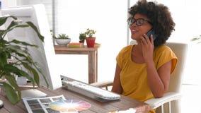 Lycklig tillfällig affärskvinna som har en påringning och använder datoren arkivfilmer