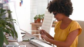 Lycklig tillfällig affärskvinna som smsar och använder datoren arkivfilmer