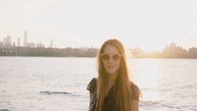 Lycklig tillfällig Caucasian flicka i trendig solglasögon som poserar på kamera-, NYC-solnedgånghorisont och floden i bakgrund 4K lager videofilmer