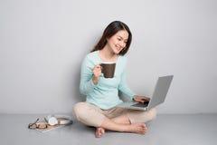 Lycklig tillfällig härlig asiatisk kvinna som arbetar på en bärbar datorsammanträdenolla Fotografering för Bildbyråer