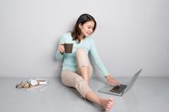 Lycklig tillfällig härlig asiatisk kvinna som arbetar på en bärbar datorsammanträdenolla royaltyfri foto