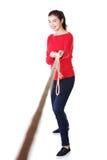Lycklig tillfällig kvinna som drar ett rep Fotografering för Bildbyråer