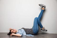 Lycklig tillfällig kvinna som ligger på golvet med lyftta ben upp över grå bakgrund och ser kameran Arkivbilder