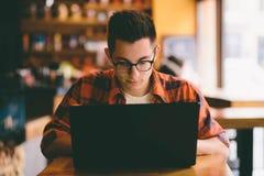 Lycklig tillfällig man som använder bärbar datordatoren Royaltyfri Fotografi