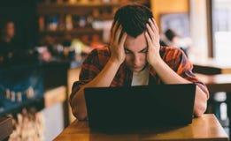 Lycklig tillfällig man som använder smartphone- och bärbar datordatoren i kafé under spänningen som förbereder sig för examina Arkivfoton