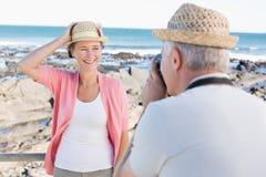 Lycklig tillfällig man som tar ett foto av partnern vid havet Arkivfoton