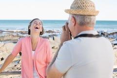 Lycklig tillfällig man som tar ett foto av partnern vid havet Arkivfoto