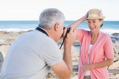 Lycklig tillfällig man som tar ett foto av partnern vid havet Arkivbild