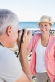 Lycklig tillfällig man som tar ett foto av partnern vid havet Royaltyfri Foto