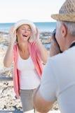 Lycklig tillfällig man som tar ett foto av partnern vid havet Royaltyfria Bilder