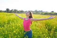 Lycklig tonårig flicka för öppna armar i våräng arkivbilder