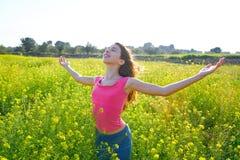 Lycklig tonårig flicka för öppna armar i våräng royaltyfri foto