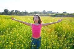 Lycklig tonårig flicka för öppna armar i våräng royaltyfri fotografi