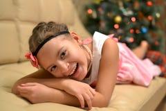 Lycklig tonårig flicka nära den dekorerade julgranen arkivfoto