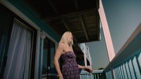 Lycklig tonårig flicka som kopplar av på lägenheterna för hotell` s på sängen Flickan låser på fönstret Lynne för sommarsemester Arkivbilder