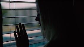 Lycklig tonårig flicka som kopplar av på lägenheterna för hotell` s på sängen Flickan låser på fönstret Lynne för sommarsemester Royaltyfria Bilder