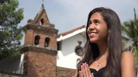 Lycklig tonårig latinamerikansk flicka som ber på kyrkan arkivfilmer