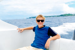 Lycklig tonårig pojke i solglasögon på yachten Tropiskt hav i bet royaltyfria bilder
