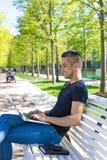 Lycklig tonåring som arbetar på netbook, medan vila in parkera i solig sommardag Man som använder applikationer arkivbild