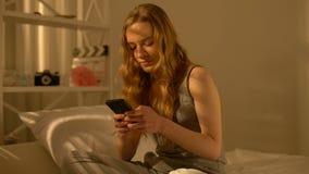 Lycklig tonåring som hemma pratar vid smartphonen, kommunikation med pojkvännen lager videofilmer