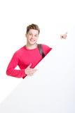 Lycklig tonåring som rymmer ett tomt baner isolerat på vit Fotografering för Bildbyråer