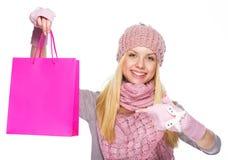 Lycklig tonåringflicka i vinterhatt som pekar på shoppingpåse Royaltyfri Foto