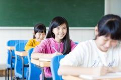 Lycklig tonåringflicka som lär i klassrumet royaltyfri fotografi