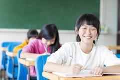 Lycklig tonåringflicka som lär i klassrumet royaltyfri bild