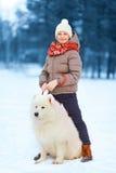 Lycklig tonåringpojke som utomhus går med den vita Samoyedhunden i parkera på en vinterdag Royaltyfri Fotografi