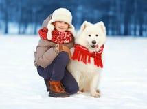 Lycklig tonåringpojke som utomhus går med den vita Samoyedhunden i vinterdag royaltyfri bild