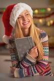 Lycklig tonårs- flicka i den santa hatten som omfamnar dagboken i kök Fotografering för Bildbyråer