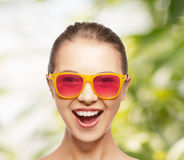 Lycklig tonårs- flicka i rosa solglasögon Royaltyfri Foto