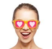 Lycklig tonårs- flicka i skuggor med hjärtor Arkivbild