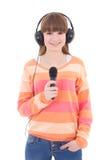 Lycklig tonårs- flicka med hörlurar och mikrofonen som isoleras på wh royaltyfri bild