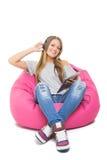 Lycklig tonårs- flicka med hörlurar och minnestavlan Arkivbild