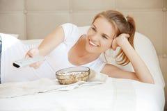 Lycklig tonårs- flicka med TVfjärrkontrollen och popcorn Royaltyfri Foto