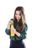 Lycklig tonårs- flicka, medan rymma en flaska av orange fruktsaft i en grön blus bakgrund isolerad white öppnar en flaska Arkivbild