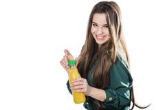 Lycklig tonårs- flicka, medan rymma en flaska av orange fruktsaft i en grön blus bakgrund isolerad white öppnar en flaska Royaltyfri Foto