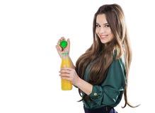 Lycklig tonårs- flicka, medan rymma en flaska av orange fruktsaft i en grön blus bakgrund isolerad white öppnar en flaska Royaltyfria Foton