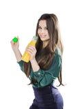 Lycklig tonårs- flicka, medan rymma en flaska av orange fruktsaft i en grön blus bakgrund isolerad white Royaltyfri Fotografi
