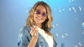 Lycklig tonårs- flicka som blåser såpbubblor som tycker om hennes lilla ofog, barndom arkivfilmer